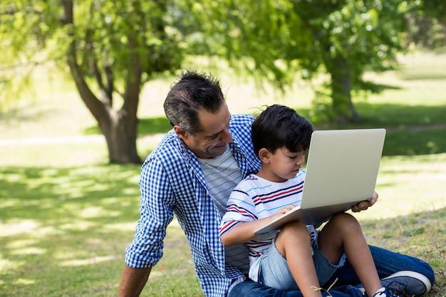 Мальчик сидит на коленях у отца и использует ноутбук в парке