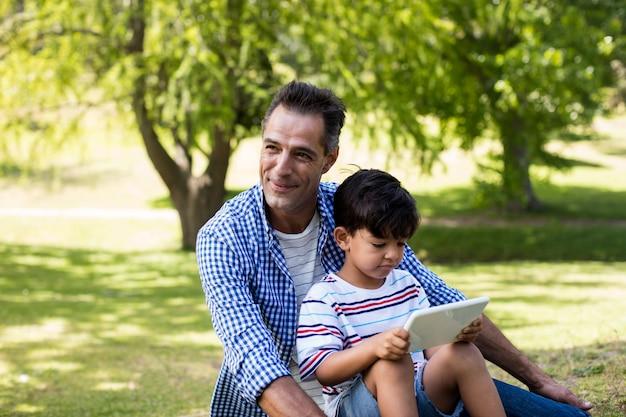 Мальчик сидит на коленях своего отца и с помощью цифрового планшета в парке