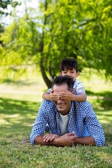 Мальчик, охватывающий глаза своего отца в парке