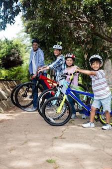 公園で自転車で立っている親と子の肖像