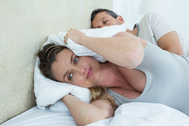 妊娠中の女性が男のいびきをかいている間彼女の耳を覆っている