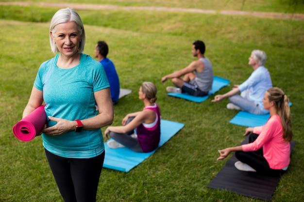 Портрет старшей женщины держа циновку тренировки пока коллеги выполняя йогу