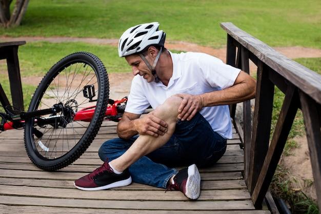 Падший велосипедист держит его поврежденное колено