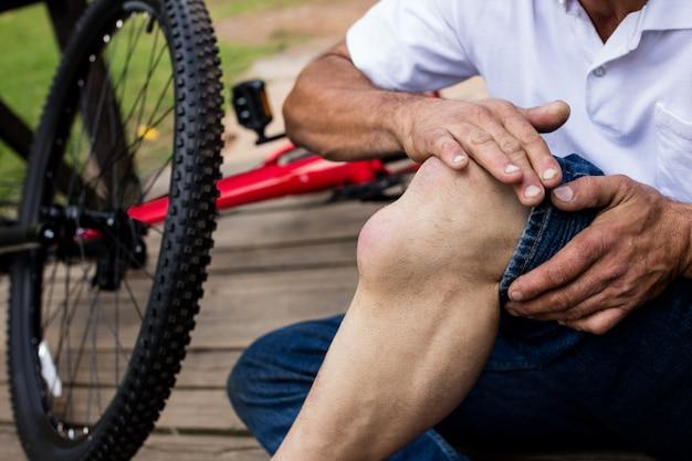 負傷した膝を抱えている転倒した自転車の中央部