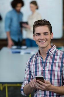 オフィスで携帯電話を使用して笑顔のビジネスエグゼクティブ