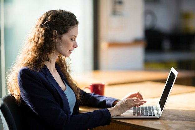 デスクでノートパソコンを使用して女性のビジネスエグゼクティブ