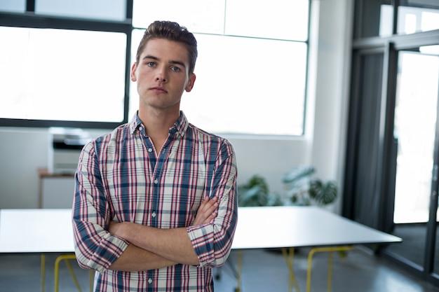 腕を組んでオフィスで立っている悲しいビジネスエグゼクティブ