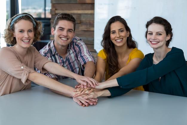 オフィスで手スタックを形成する笑顔の企業幹部のグループ