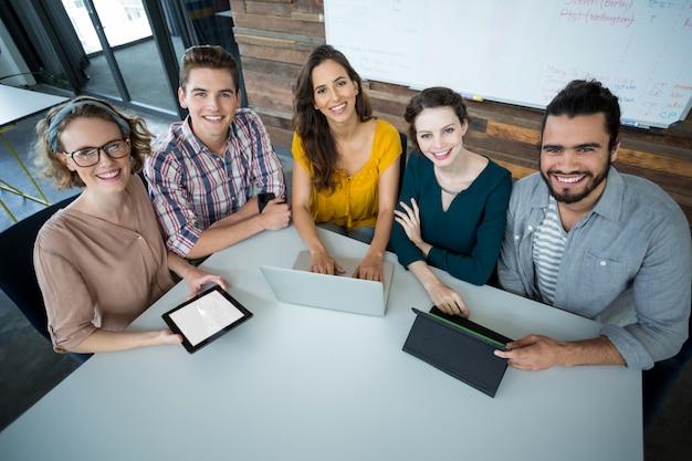 デジタルタブレットとラップトップテーブルの上でオフィスに座っている笑顔の経営者