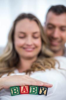 彼女の腹と彼女の夫の自宅のソファーに横になっている赤ちゃんキューブと妊娠中の女性
