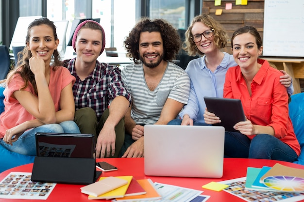 ノートパソコンとデジタルタブレットのテーブルの上でオフィスに座っている笑顔のグラフィックデザイナー