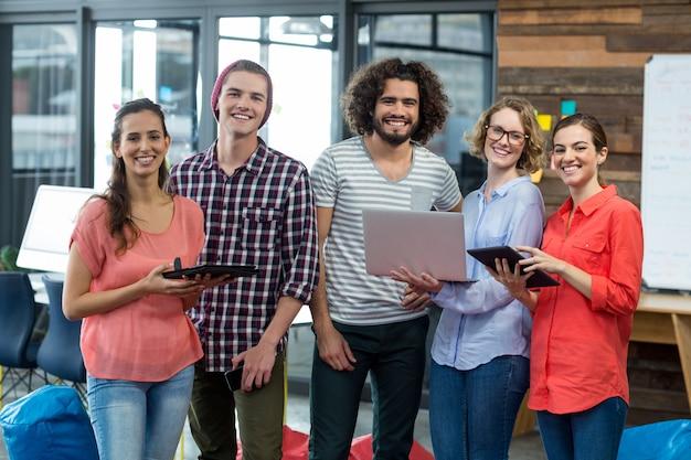 Улыбающиеся руководители бизнеса, стоя в офисе с цифровым планшетом и ноутбуком