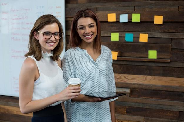 Руководители бизнеса стоя с цифровой таблеткой и кофейной чашкой в офисе