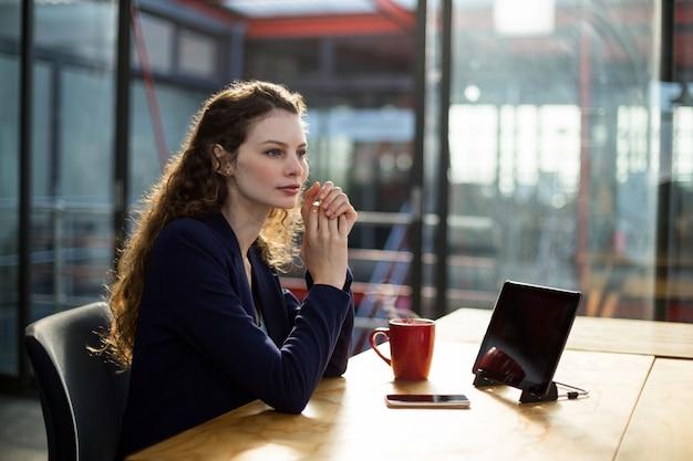 Вдумчивые руководители предприятий, сидя с цифровой планшет и чашка кофе на столе