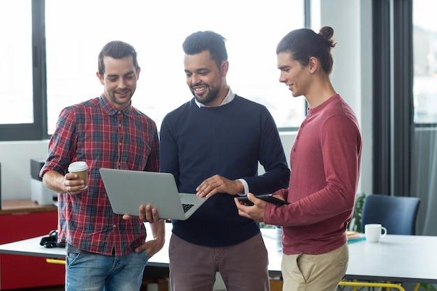 Бизнесмены, имеющие обсуждение на ноутбуке