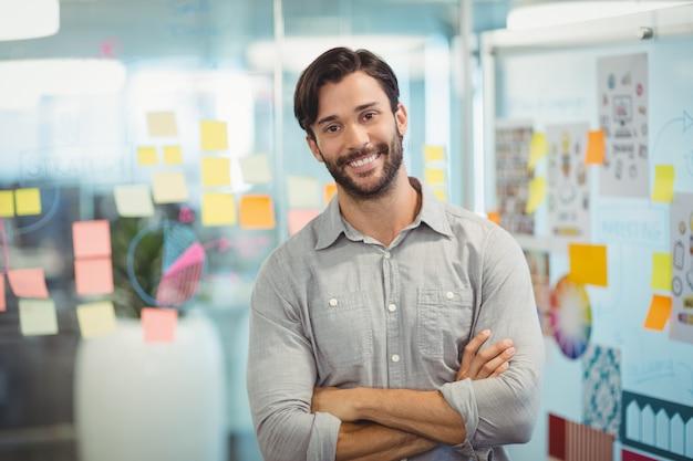腕を組んでオフィスで立っている男性のビジネスエグゼクティブ