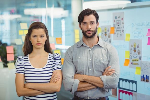 腕を組んで立っている男性と女性の企業幹部の肖像画