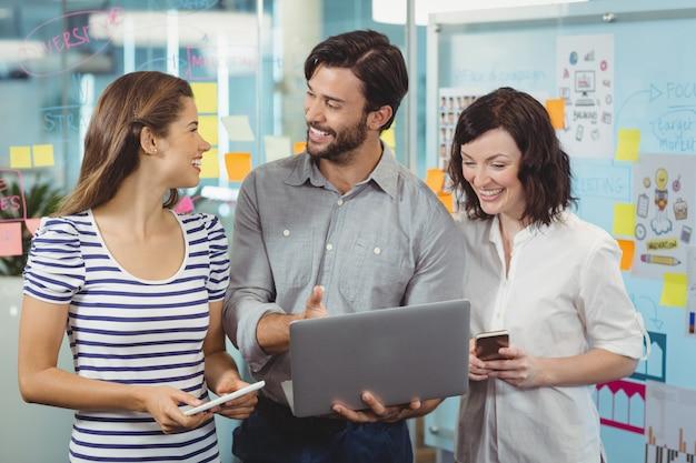 ノートパソコンで議論する経営幹部のチーム