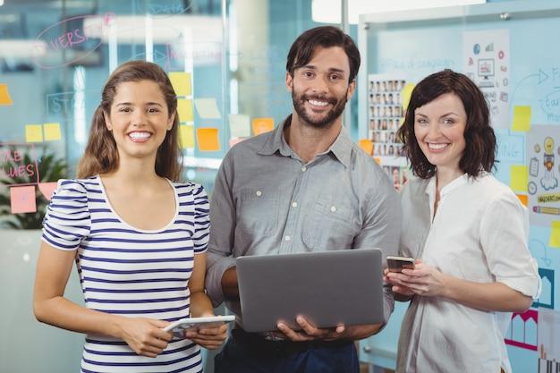 オフィスで一緒に立っている経営者のチーム