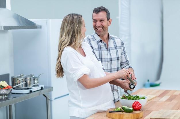 妊娠中のカップルが台所でサラダを準備します。