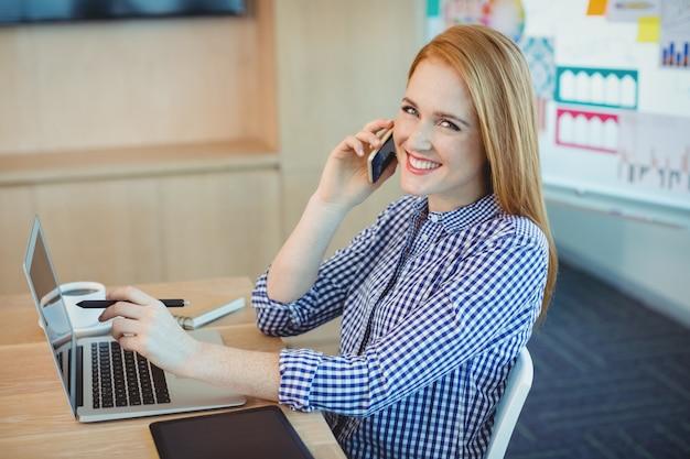 Женский графический дизайнер разговаривает по мобильному телефону во время работы в офисе
