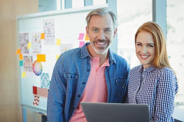 ラップトップを保持している男性と女性のビジネスエグゼクティブの肖像画