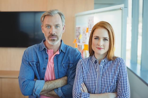 会議室で腕を組んで立っている男性と女性の企業幹部の肖像画