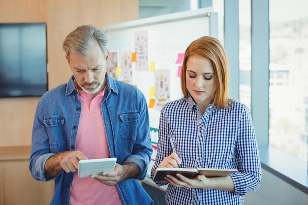 男性の幹部がデジタルタブレットを使用しながら女性の幹部が日記に注意