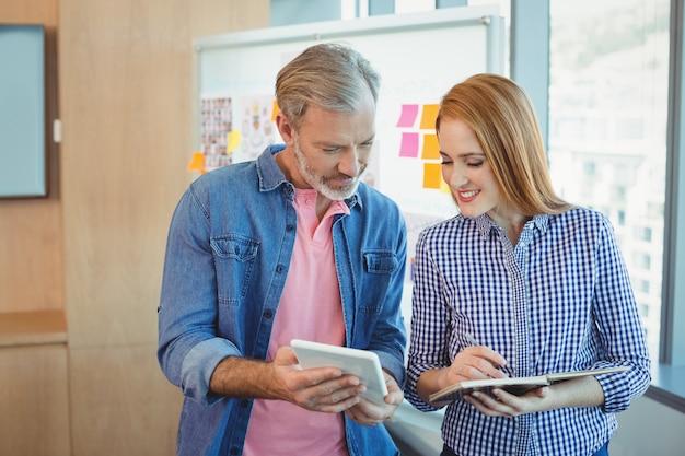 男性の幹部がデジタルタブレットを使用しながら女性の幹部が日記を書いている