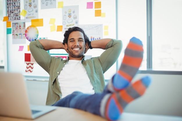 男性のグラフィックデザイナーが足を机に向かってリラックス