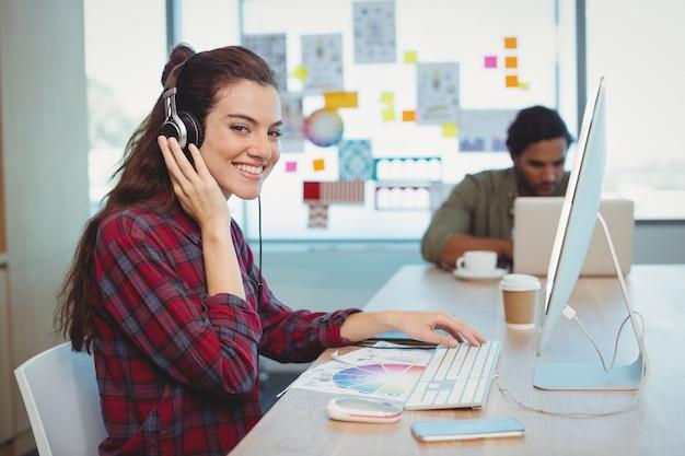 音楽を聴きながら働く女性のグラフィックデザイナー