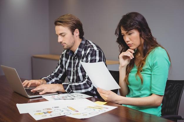 会議室で一緒に働く男性とグラフィックデザイナー