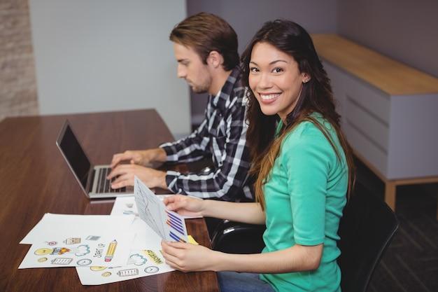 Мужской и графический дизайнеры, работающие вместе в конференц-зале