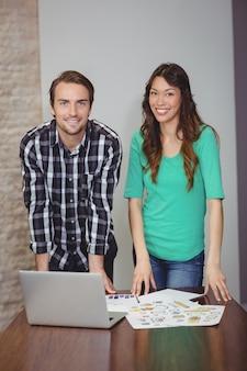 Портрет мужчины и женщины графических дизайнеров, стоя в конференц-зале