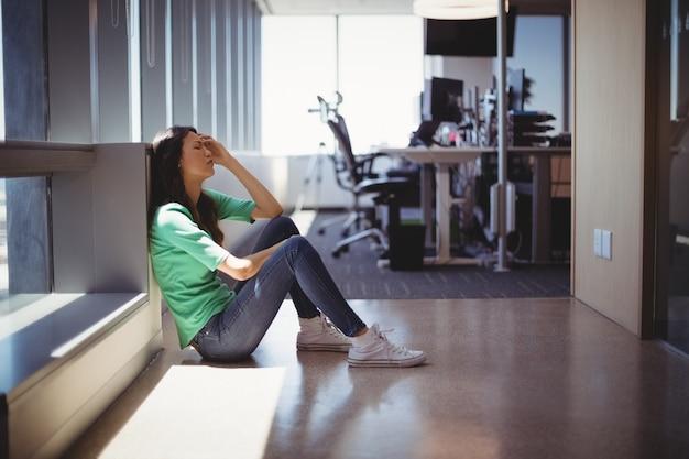廊下に座っている心配している女性幹部