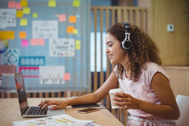 Женский графический дизайнер прослушивания песни при использовании ноутбука