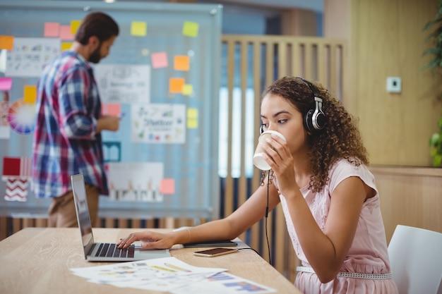 Женский графический дизайнер пьет кофе при использовании ноутбука