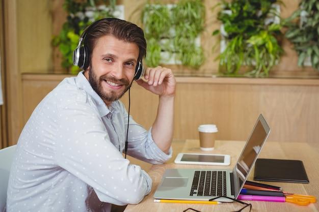 Портрет мужского руководителя бизнеса сидя с компьтер-книжкой и слушая песней
