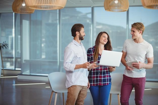 Счастливые руководители бизнеса с помощью цифрового планшета и ноутбука