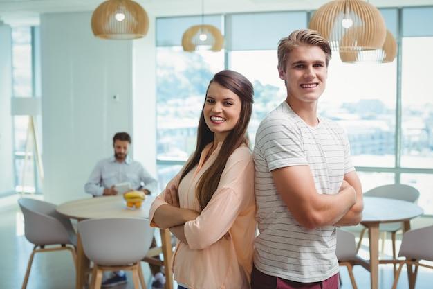 Счастливые руководители бизнеса, стоя спиной к спине в офисе