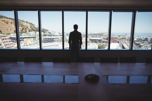 窓から見ている男性のビジネスエグゼクティブ