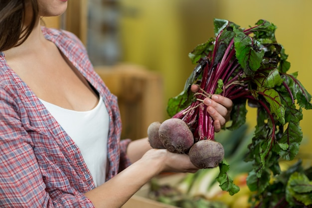 Женщина выбирая овощи в продуктовом магазине