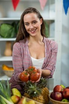 カウンターでトマトを提供している笑顔の女性ベンダー