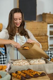 Улыбающиеся женщина сотрудников положить круассан в бумажный пакет на стойке