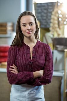 腕を組んでカウンターに立っている笑顔の女性スタッフの肖像画