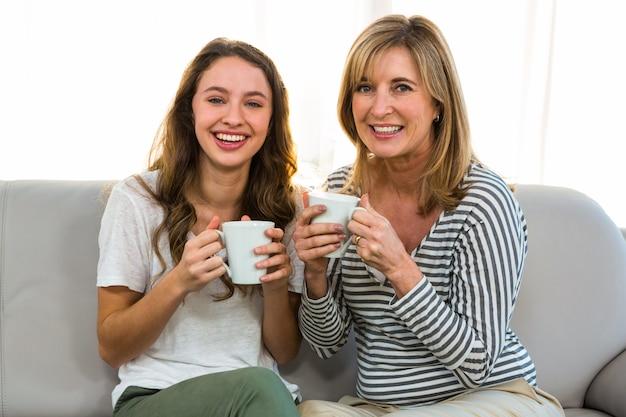 母と娘が家でお茶を飲む