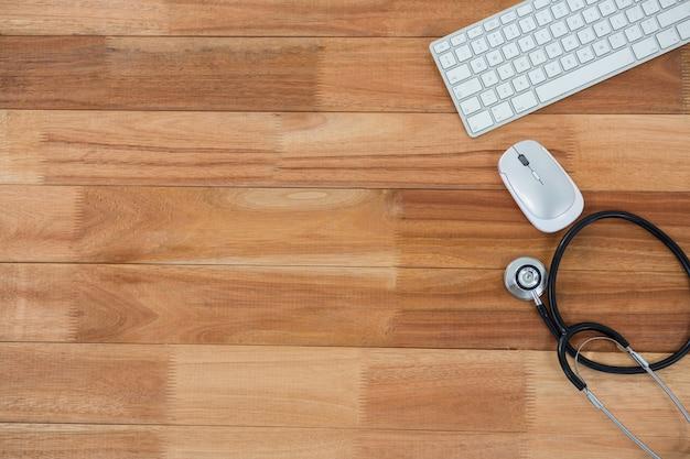 キーボードとマウスの木製の背景を持つ聴診器
