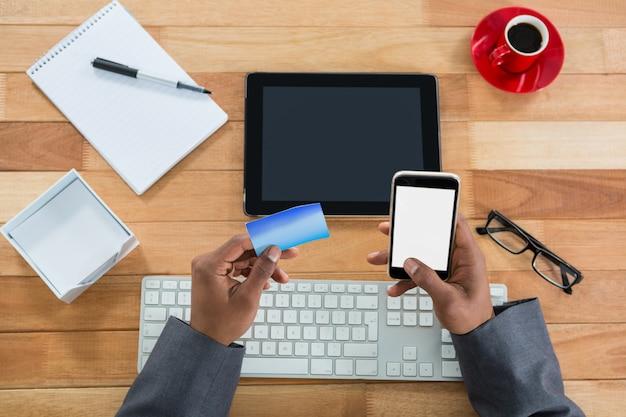 携帯電話でオンラインショッピングを行うビジネスマン