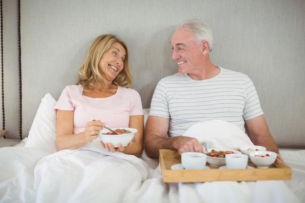 ベッドで朝食を持っている笑顔のカップル