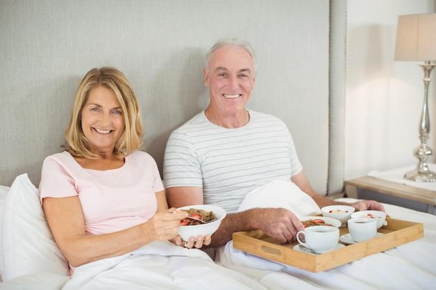 ベッドで朝食を食べて笑顔のカップルの肖像画